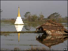 A small temple is seen submerged in a flooded rice field near a house destroyed by Cyclone Nargis, near Rangoon
