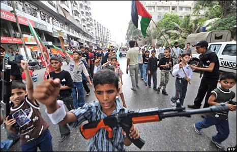 Pakistani Shia Muslim boys carry toy guns at a rally in Karachi