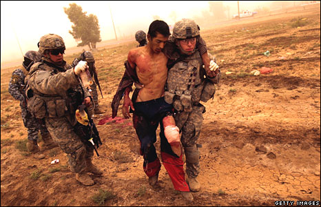 US troops treat a man shot in the leg after he fled a US patrol in Baghdad