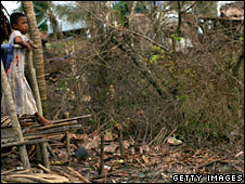 A girl looks at what's left of her home in a village outside Rangoon, 16 May, 2008