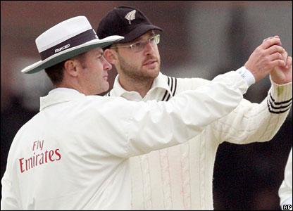 Umpire Simon Taufel and New Zealand captain Daniel Vettori consult Taufel's light meter