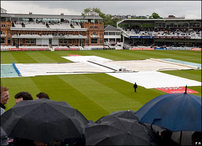 The Lord's pitch is covered as spectators raise their umbrellas