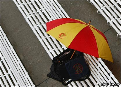 An MCC umbrella and bag on a bench in the pavilion