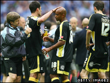 Terry Burton, assistant manager of Cardiff City, consoles player Trevor Sinclair