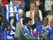 Portsmouth's Sol Campbell, left, lifts the trophy as he celebrates with teammates after beating Cardiff City 1-0 to win the FA Cup final
