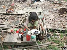 A homeless girl tries to salvage some items from her destroyed house near Rangoon. Photo: 17 May 2008