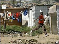 A man runs from South African police as they take up positions in the Diepsloot township north of Johannesburg 15 May 2008