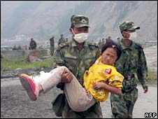 Chinese troops rescue an injured survivor from Wenchuan county, Sichuan province on 18 May 2008
