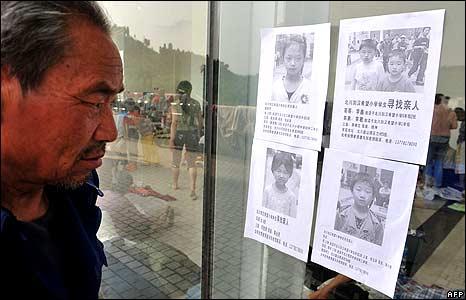 Man examining posters of missing children at Beichuan stadium 18/5/08