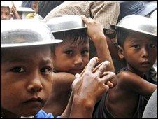 Burmese children shelter from the rain under empty plates