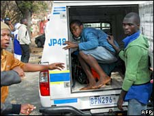 A foreigner (centre) boards a police van on 18 May, 2008 to be escorted safely out of Jeppestown in Johannesburg