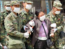 Soldiers escorting a woman in distress after the earthquake in China