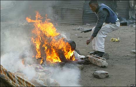 A policeman tries to help a man who was set alight in Johannesburg. Photo: 18 May 2008