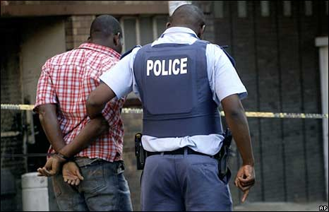 A police officer detains a man in Johannesburg on 18 May 2008
