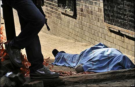 A policeman stands by the body of a man killed in Johannesburg. Photo: 18 May 2008