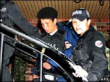 Nelly Avila Moreno, known as Karina, (left) is escorted by police officers in Colombia on 18 May 2008