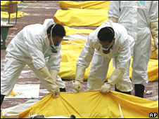 Workers collect body bags at Hanwang, Sichuan province, 16 May 2008