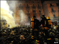 Italian firefighters try to extinguish burning, uncollected rubbish in a street in the centre of Naples