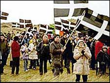 People wave the St Piran (the patron saint of Cornwall) flag