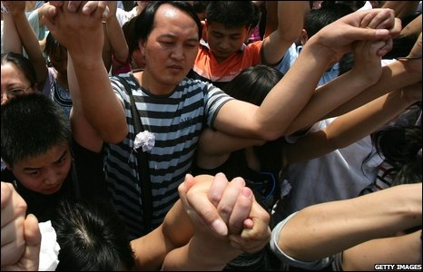 People in main square in Chengdu hold hands for the three-minute silence
