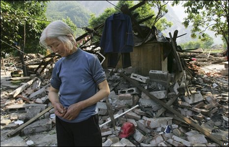 Woman stands by ruins of home in An county