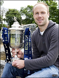 Queen of the South midfielder Neil MacFarlane poses with the cup