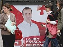 Прохожие в Тбилиси на фоне предвыборного плаката кандидата от партии, поддерживающей президента Михаила Саакашвили