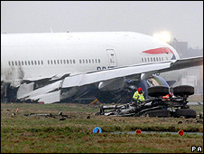 British Airways Boeing 777 plane lies at the foot of the Southern runway after its crash landing