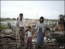 A family stand in the ruins of their house in Kyauktan on 16 May 2008