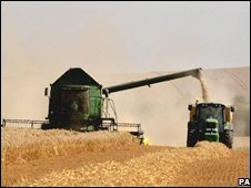 Combine harvester and tractor on farm near Cambridge, UK - photo 23 April