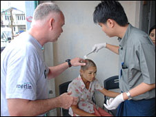 Dr Sean Keogh (L) treats a child in the Irrawaddy delta