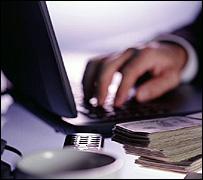 Mano escribiendo en computador con dinero al lado.
