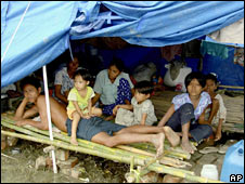 Survivors of Cyclone Nargis rest inside their makeshift shelter in Burma