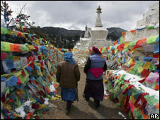 Two Tibetan women walk past prayer flags and stupa at Feilaisi, near the border with Tibet