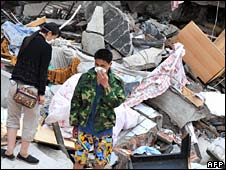 Residents cover their noses as they search through rubble in Beichuan on 20 May 2008