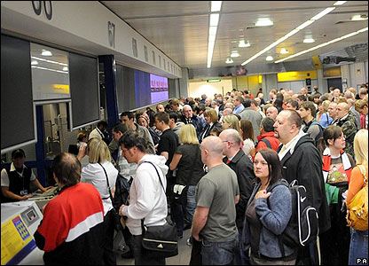 Manchester United fans queue at the check-in desks before boarding their flights to Moscow from Manchester Airport