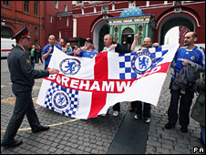 A policeman addresses a group of Chelsea fans