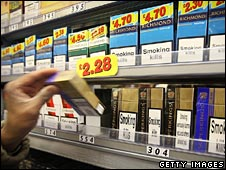 Packet of cigarettes being taken off a display shelf