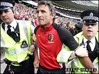 Toulouse coach Guy Noves is escorted out of Murrayfield by police in 2005