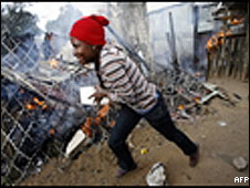 A woman runs as she tries to extinguish a fire in a burning shack during violent xenophobic clashes at Reiger park informal settlement on the outskirt of Johannesburg