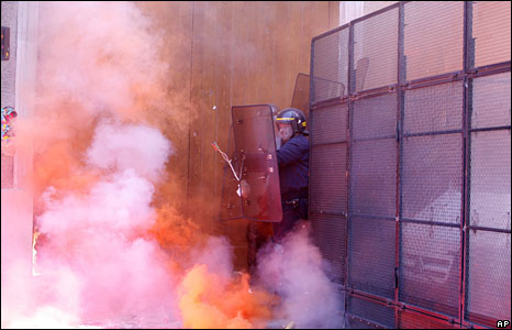 A policeman shields himself from flares near the agriculture ministry in Paris, 21 May 2008