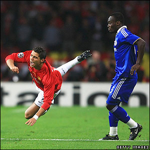 Michael Essien watches as Ronaldo goes down