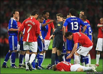 Scholes holds his head after the collision