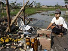 A woman looks for her belongings at her damaged home outside Rangoon on 21 May 2008