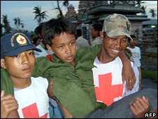 Red Cross volunteers carry an injured boy on 21 May 2008 (Image: IFRC)