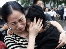 A woman, left, cries as she consoles her relative who survived the earthquake from the devastated Wenchuan county after they air lifted at the Phoenix airbase in Chengdu
