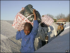 Immigrants carry belongings as they leave an informal refugee camp in Primrose, Johannesburg, 22 May 2008
