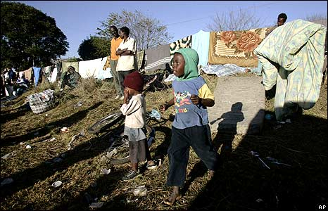 People standing in temporary refugee camp at Primrose police station, Johannesburg