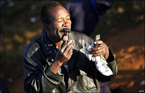 Man shaving in temporary refugee camp at Primrose police station, Johannesburg 
