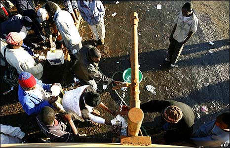 People collecting water in temporary refugee camp at Primrose police station, Johannesburg